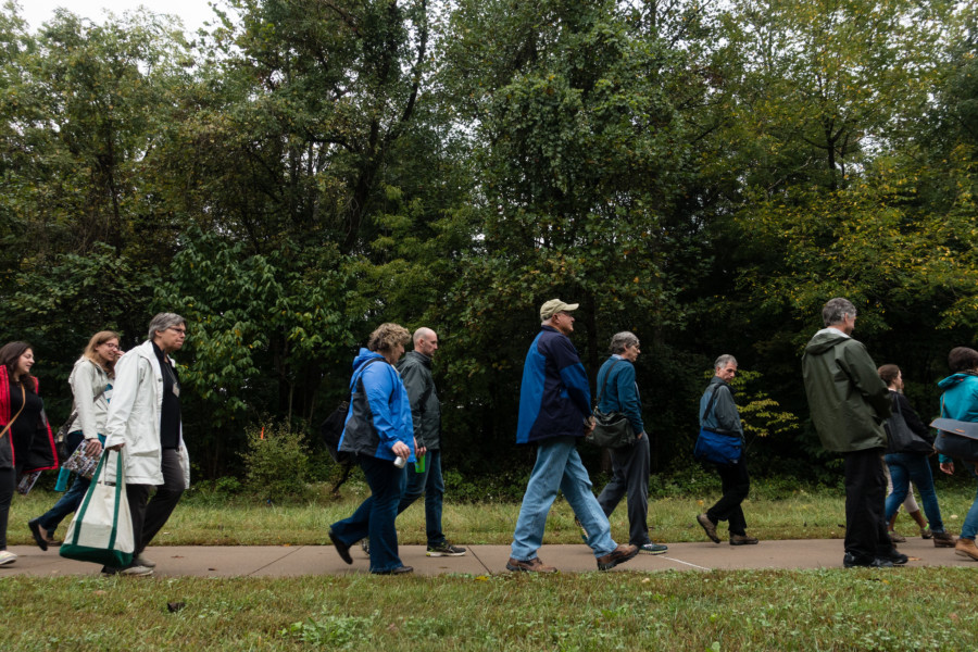 A group of people walk along the path between Instructional Halls East and West at the National Conservation Training Center in cold weather gear.