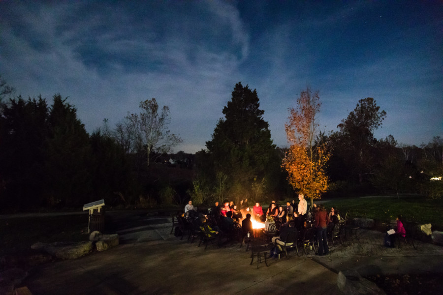 A group of people hang out around a bonfire at the National Conservation Training Center.